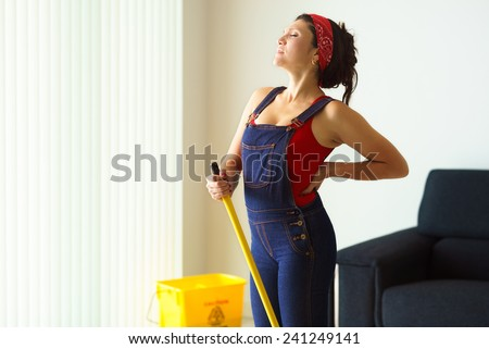 Happy young hispanic woman at home, doing chores and housekeeping, suffering pain in the back - stock photo