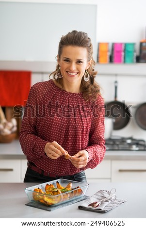 Happy young housewife adding garlic to baked pumpkin - stock photo