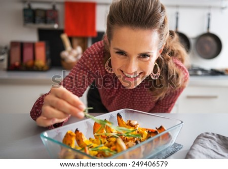Happy young housewife adding rosmarinus to baked pumpkin - stock photo