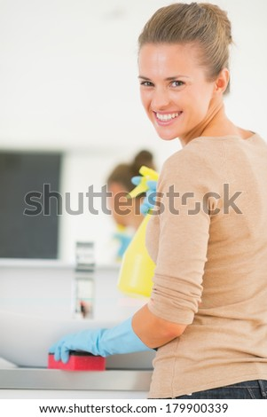 Happy young housewife cleaning in bathroom - stock photo