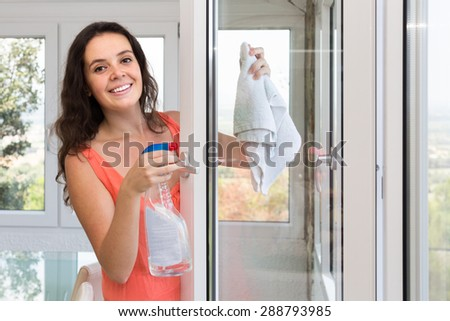 Happy young housewife cleaning windows using atomizer indoor