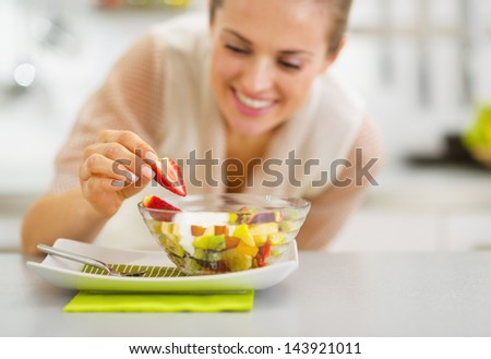 Happy young housewife decorating fruits salad - stock photo