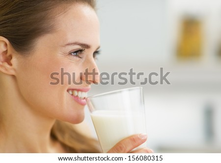 Happy young housewife drinking milk - stock photo