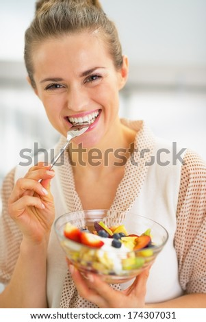 Happy young housewife eating fresh fruit salad - stock photo