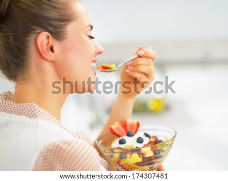 Happy young housewife eating fresh fruit salad in kitchen. rear view - stock photo