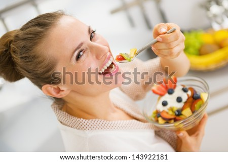 Happy young housewife eating fruits salad . rear view - stock photo