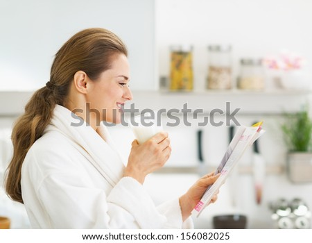 Happy young housewife in bathrobe drinking milk and reading magazine - stock photo