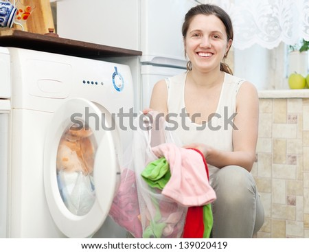 Happy young housewife in white doing laundry at her home