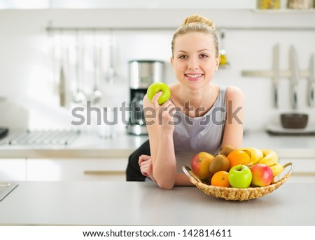 Happy young housewife with apple in modern kitchen - stock photo