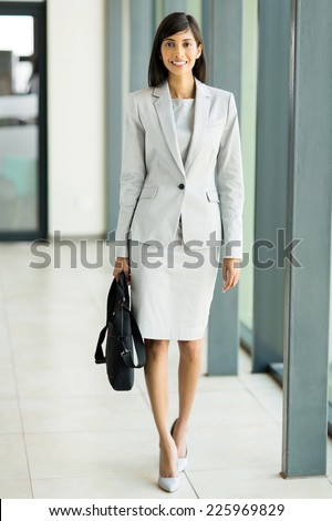 happy young indian businesswoman with briefcase in office building - stock photo