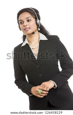 Happy young Indian call centre employee smiling with a headset over white
