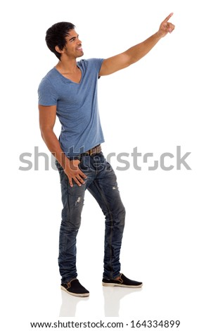 happy young indian guy pointing up over white background - stock photo
