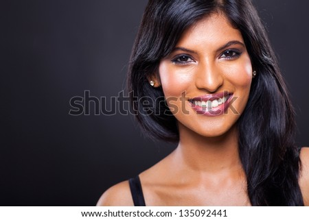 happy young indian woman against black background - stock photo