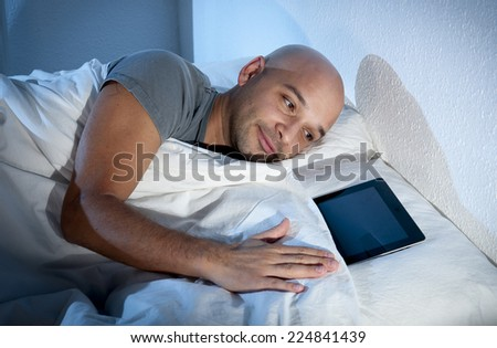happy young internet addict man awake late at night in bed sleeping with digital pad or tablet as funny metaphor of online digital devices addiction and abuse concept