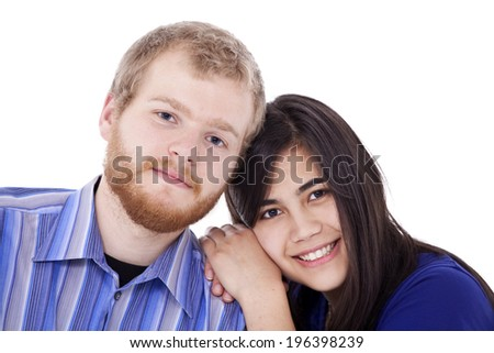 Happy young interracial couple in blue, early twenties or late teens, studio shot - stock photo