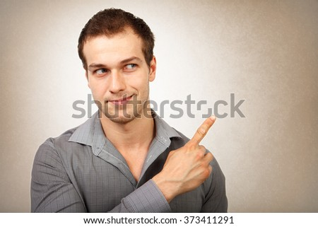 Happy young isolated man pointing finger - stock photo