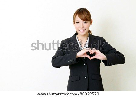 Happy young japanese business woman make heart shape by her hands - stock photo