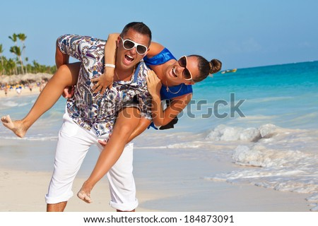 Happy young joyful couple having beach fun piggybacking laughing together during summer holidays vacation on Caribbean tropical beach. Beautiful fashion energetic couple.  - stock photo