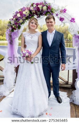 Happy young just married couple standing under floral gates at wedding ceremony - stock photo