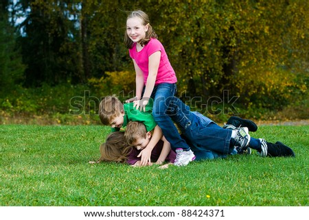 Happy young kids playing outside piled on top of each other on a field of grass. - stock photo