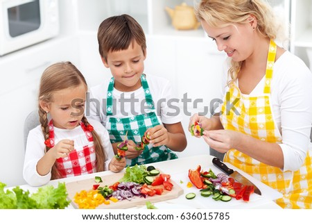 Happy young kids with their mother in the kitchen - preparing a healthy snack, top view closeup