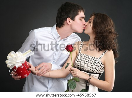 Happy young kissing couple with gift and red rose - stock photo