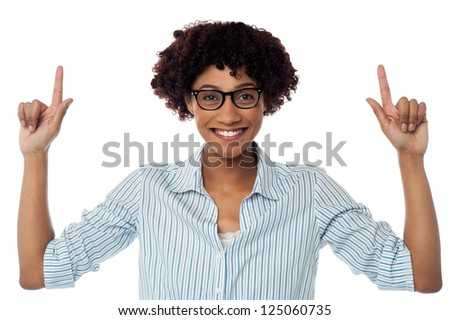 Happy young lady in spectacles gesturing upwards with both her hands.