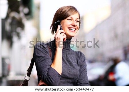 Happy young lady talking on mobile phone - stock photo