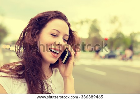 Happy young lady talking on mobile phone walking on a street  - stock photo