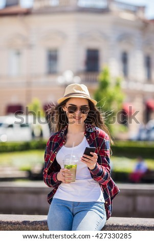 Happy young lady text on mobile phone on the street - stock photo