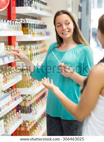 Happy young longhaired woman selecting perfume in the store