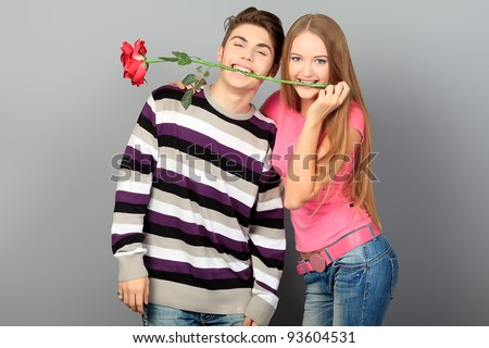 Happy young love couple posing together with red rose.
