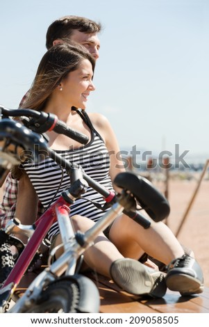 Happy young lovers with bikes on beach at summer day