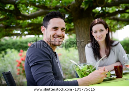 happy young loving couple having lunch at barbecue party outdoor in the garden - stock photo