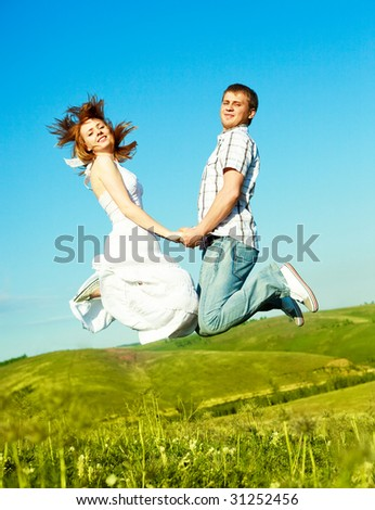 happy young loving couple jumping outdoor in summertime - stock photo