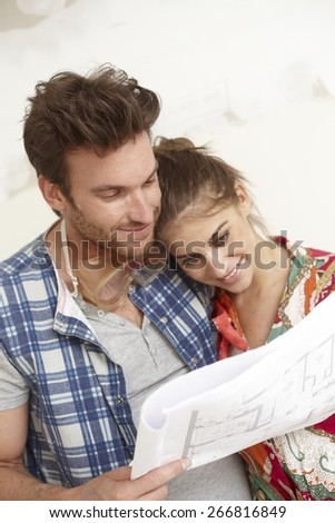 Happy young loving couple planning a new home, looking at floor plan in home under construction. - stock photo