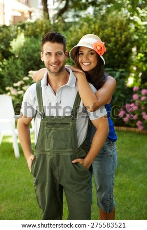 Happy young loving couple smiling outdoors, embracing, looking at camera. - stock photo
