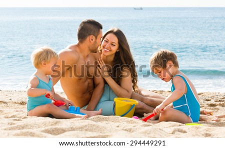 Happy young loving parents with two kids playing with sand at beach