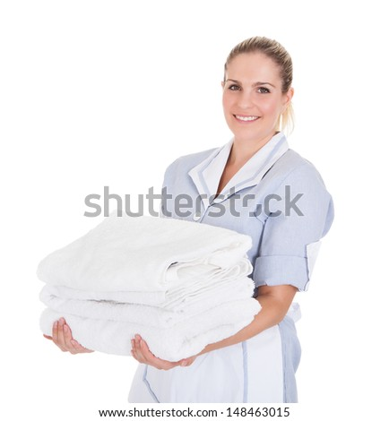 Happy Young Maid Holding Towels Over White Background - stock photo