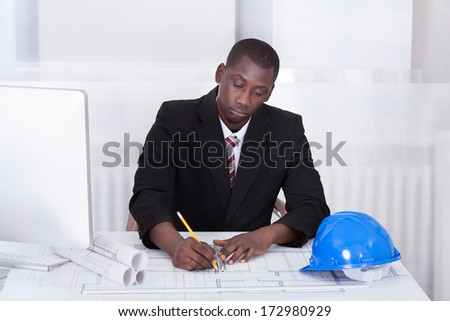 Happy Young Male African Architect Drawing Blueprint - stock photo