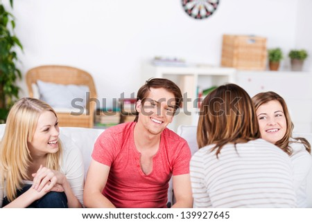 Happy young male and female friends spending time together at home - stock photo