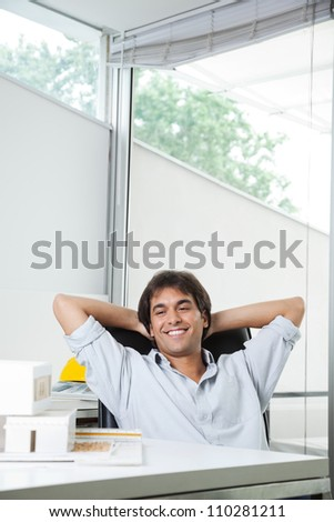 Happy young male architect looking at model house while sitting in chair with hands behind head - stock photo