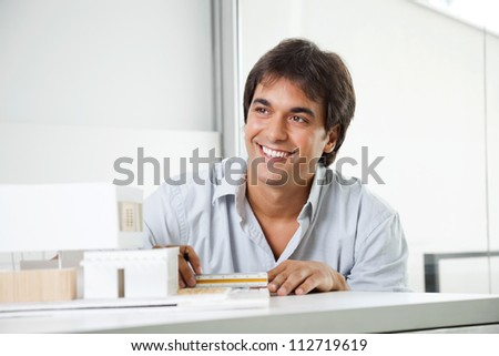 Happy young male architect looking away while creating a model house - stock photo