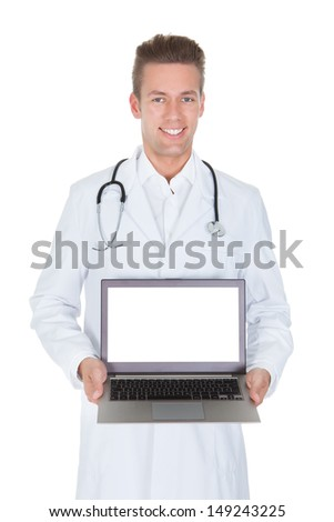 Happy Young Male Doctor Holding Laptop Over White Background - stock photo
