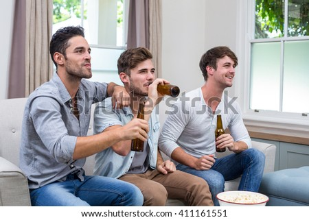 Happy young male friends drinking beer while watching TV at home - stock photo