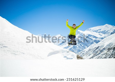 Happy young male hiker jumping in white snowy winter mountains Himalayas.  Success climbing on snow, beautiful landscape with Annapurna peak in background - stock photo
