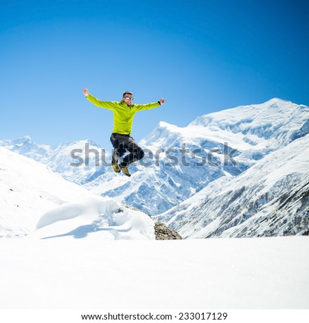 Happy young male hiker jumping in white winter mountains Himalayas, inspirational landscape.  Success climber climbing on snow, beautiful landscape with Annapurna peak in background - stock photo