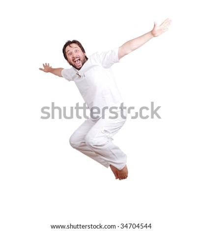 Happy young male in white clothes is jumping with hands up