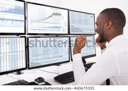 Happy Young Male Stock Market Broker Looking At Graphs On Multiple Computer In Office