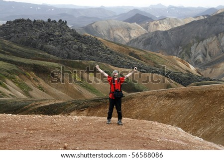 Happy young male traveller, photographer enjoying the beautiful view of mountains in Landmannalaugar region, Iceland - stock photo